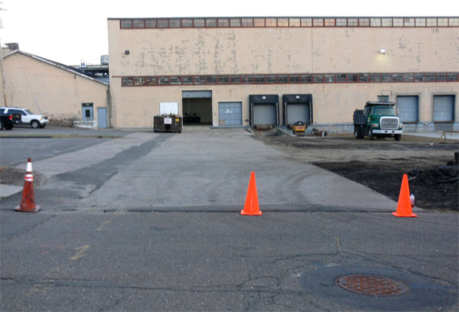 "A view of the unused section of Hull Street, looking toward the Inline Plastics factory. The roadway covers the lighter colored asphalt area in the parking lot, going toward the building. In recent days, Inline Plastics has been rebuilding its parking lot near the ""paper road"" that is Hull Street."