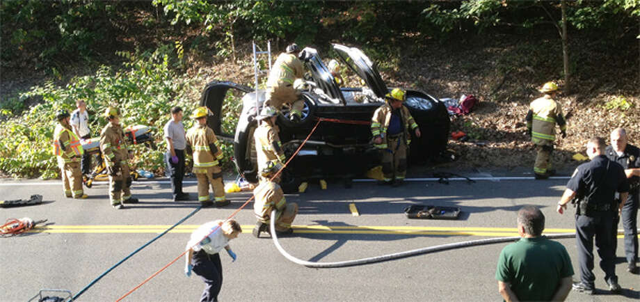 Shelton firefighters work to extricate an occupant of a SUV that landed on its side on Mohegan Road. (Submitted photo)