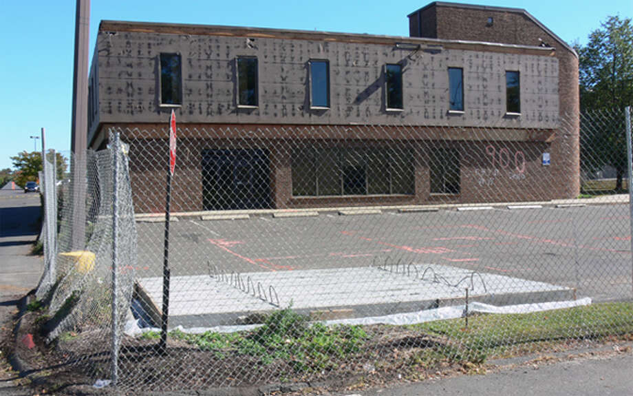 A chain-link fence has been put around the building that will be demolished to build a Stop & Shop gas station.
