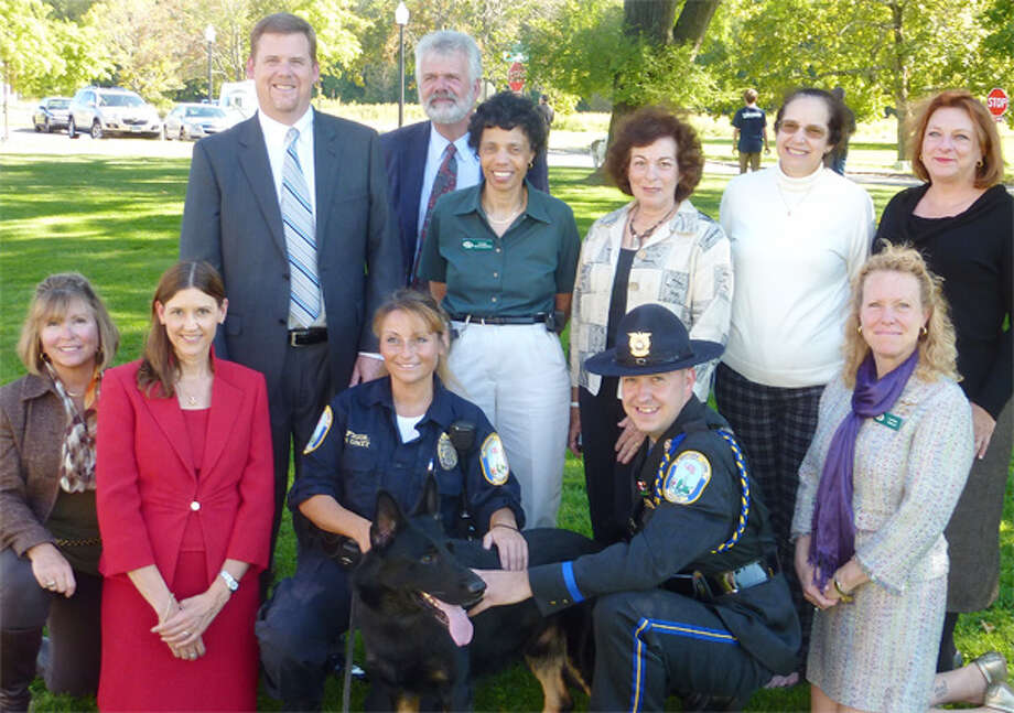 "Shown from left, bottom: Trap Falls Kennel Club (TFKC) member Cindy Sherman, American Kennel Club (AKC) Communications Director Lisa Peterson, Newtown police officer and K-9 handler Felicia Figol, K-9 dog ""Saint,"" Newtown police officer Matt Hayes, TFKC President Laura Wells; and top: TFKC member Chris Sweetwood, AKC Reunite CEO Tom Sharp, and TFKC members Cindy Richardson, Lauren Friedman, Jan Miller and Sarah Murphy."