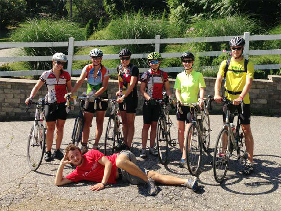 After spending the night at the home of Kate Pipa's parents during the cross-country ride, the Ride Against AIDS crew prepares to ride out of Shelton on Aug. 19 toward Hartford. Shown, from left, are Kate Pipa of Shelton, Amanda Feairheller, Dana Ballard, Lisa Fawcett, Laura Karson, Maxwell Smith; lying down is Eric Steinbrook.