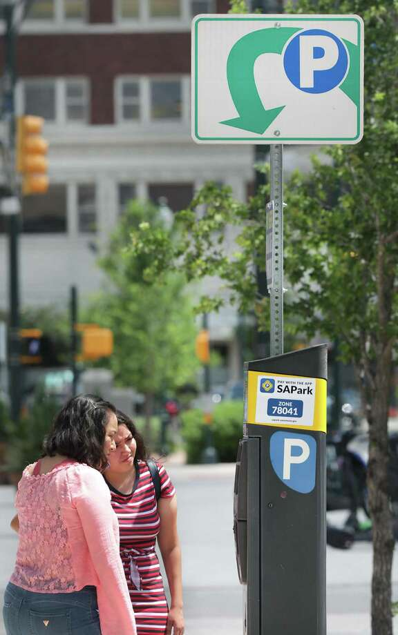 Griselda Aguilar, left, and Marisol Muniz read the instructions on a parking ticket dispenser on N. Main St. on Wednesday, June, 5, 2019. Photo: Bob Owen, Staff Photographer / Staff Photographer / ©2019 San Antonio Express-News
