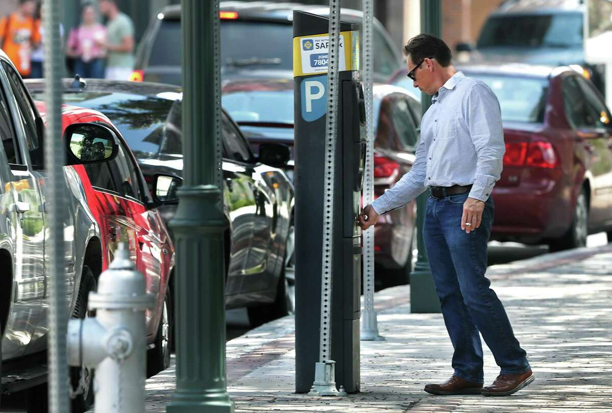 Steve Rico pulls his receipt from a parking ticket dispenser on N. Main St. on Wednesday, June, 5, 2019.