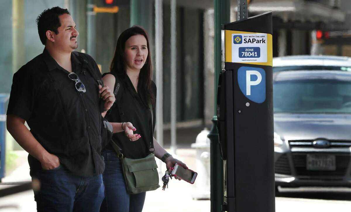 Meghan Garza, right, and Juan Cano wait for the parking ticket dispenser to spit out a receipt on N. Main St. on Wednesday, June, 5, 2019.
