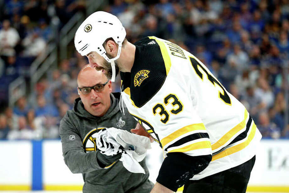 Boston Bruins defenseman Zdeno Chara is helped off the ice after getting hit in the face with the puck Monday night in Game 4 of the Stanley Cup Final against the Blues in St. Louis. Photo: Jeff Roberson | AP Photo