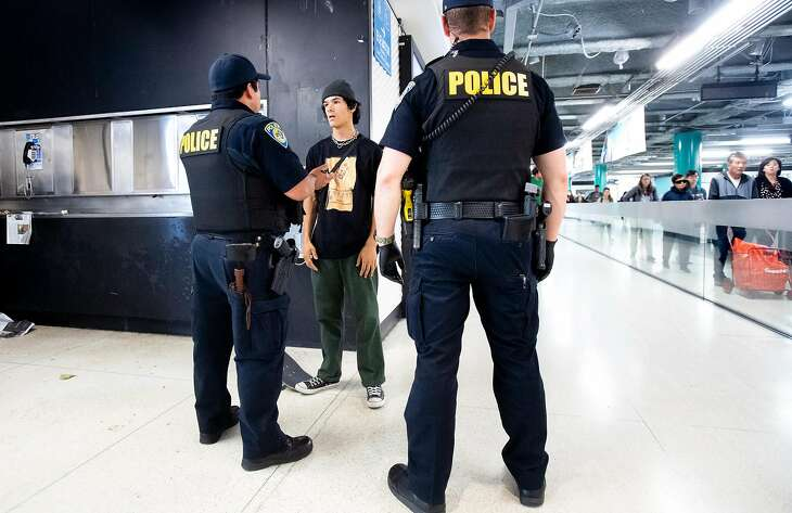 BART police officers question Austin Alvarado for not having a ticket at the Powell Street station on Wednesday, June 5, 2019, in San Francisco. Alvarado received a warning, but no citation, after he purchased a ticket.