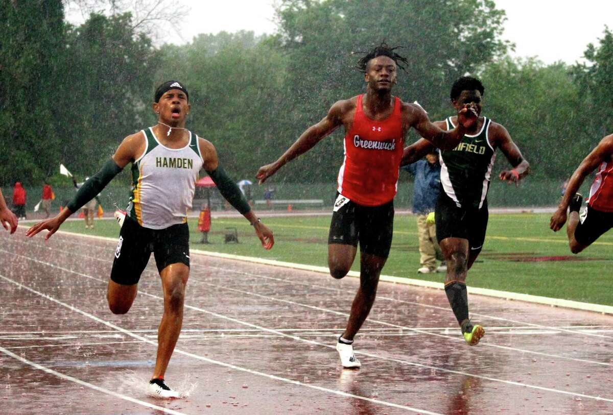 Greenwich's Ryan Raybuck, center, crosses the finish in the 100-meter dash finals during Class LL Track and Field Championships on May 29 in New Britain.