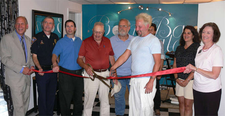 Dignitaries and the owners line up for the ribbon cutting ceremony inside the new Bomba Salon in Shelton.
