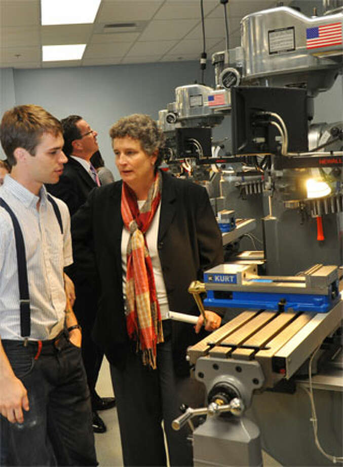HCC advanced manufacturing program graduate Chris Heun chats with state Sen. Beth Bye while Gov. Dannel P. Malloy, center, checks out some of the machinery in HCC's new Regional Advanced Manufacturing Lab.
