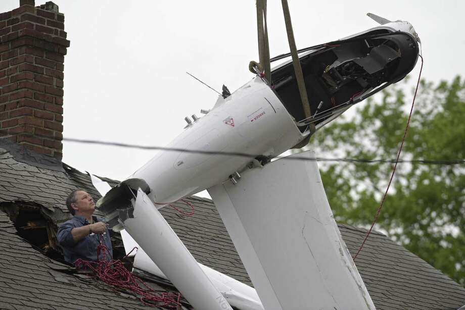 Chris Cunningham, General Manager/Director of Maintenance of Colonial Air in New Bedford, MA, secures a glider to a crane brought in to remove the 2016 Alisport Silent 2 Electro glider from the roof of a house on Golden Hill Avenue. The glider crashed through the roof of the house on Tuesday evening. June 5, 2019, in Danbury, Conn. Photo: H John Voorhees III / Hearst Connecticut Media / The News-Times