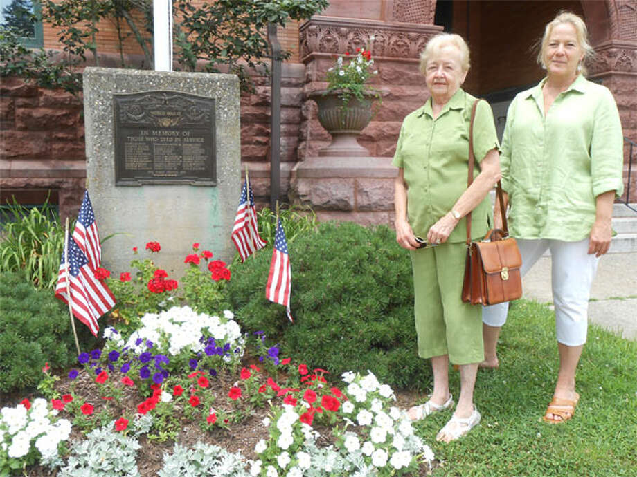 Joyce Donnelly, left, Olde Ripton Garden Club president, and Renee Marsh, vice president, stand near the holiday garden planted in front of Plumb Memorial Library. (Photo by Karen Kovacs Dydzuhn)