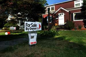 """A house on Judd Street in Fairfield, Conn. displays a """"For Sale by Owner"""" sign on Tuesday, Oct. 15, 2013."""