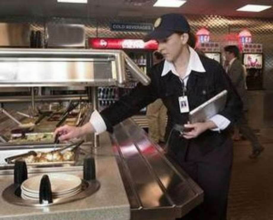 A health inspector checks the temperature of food at a buffet.