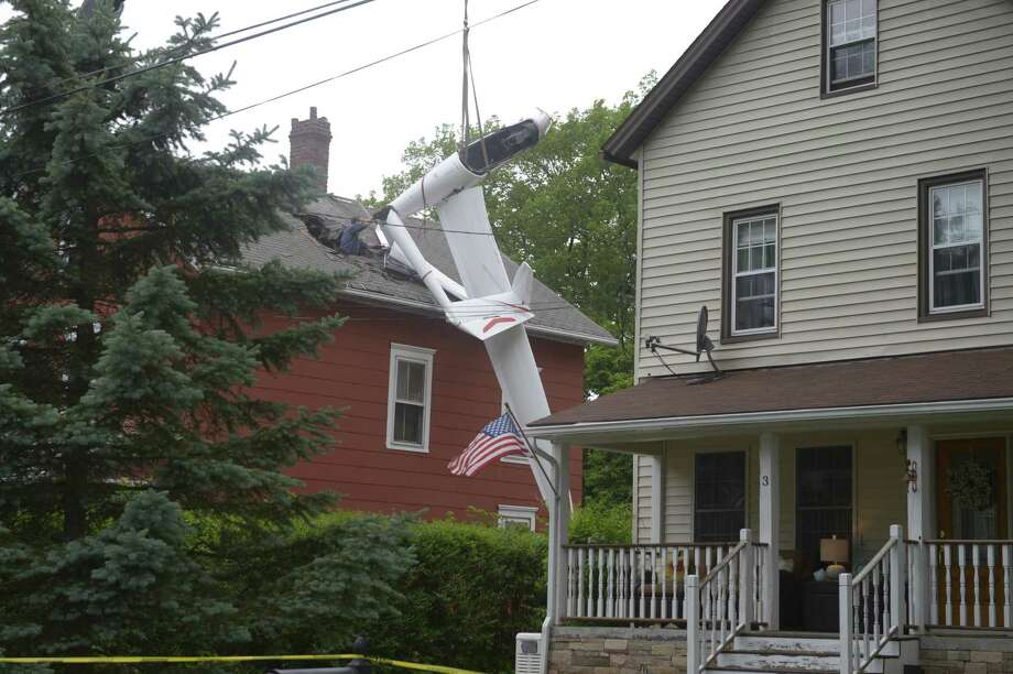 A crane from Healy Crane was brought in to remove a 2016 Alisport Silent 2 Electro glider from the roof of a house on Golden Hill Avenue Wednesday.cJune 5, 2019, in Danbury, Conn. Photo: H John Voorhees III / Hearst Connecticut Media / The News-Times