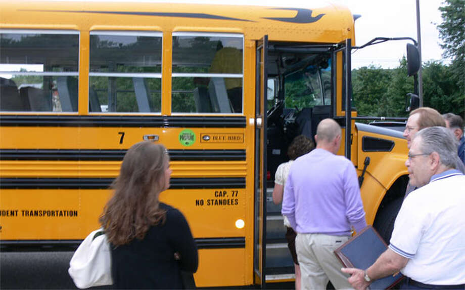 Educators, school board members and others check out the new propane-fueled bus.