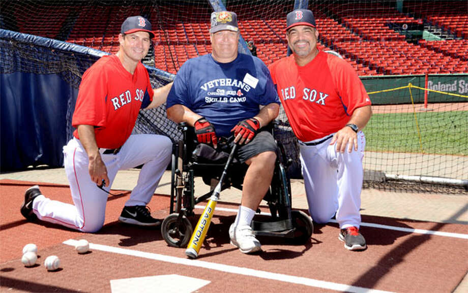 Boston Red Sox hitting coach Greg Colbrunn, left, and assistant hitting coach Victor Rodriguez with military veteran George Eldridge of Shelton on the field at Fenway Park. (Photos by Constance Brown)
