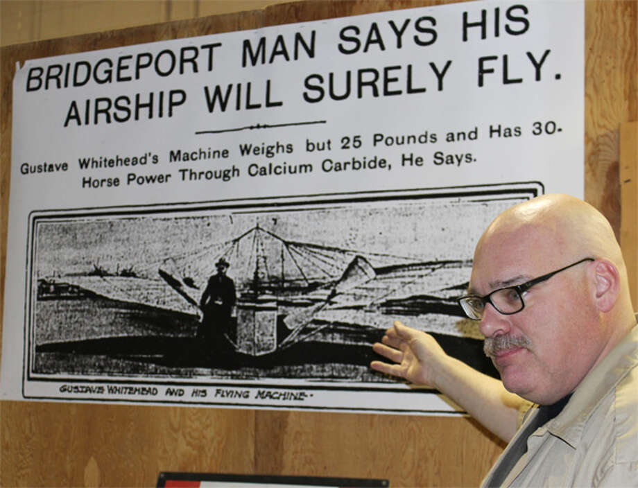 Andrew King, chief executive officer of the Connecticut Air and Space Center in Stratford, discusses early coverage of Gustave Whitehead's attempts to fly in front of an enlargement of a front page at the time. The dimensions in the headline are erroneous, King said. (Photo by John Kovach)