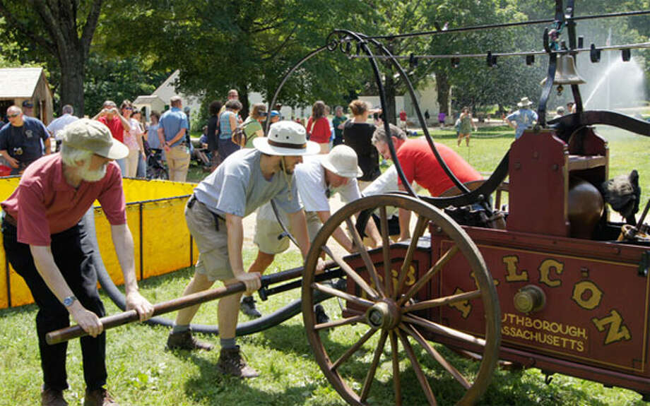 Men pump a Falcon hand tub, used to battle fires in the 1800s, at Old Sturbridge Village in Massachusetts.