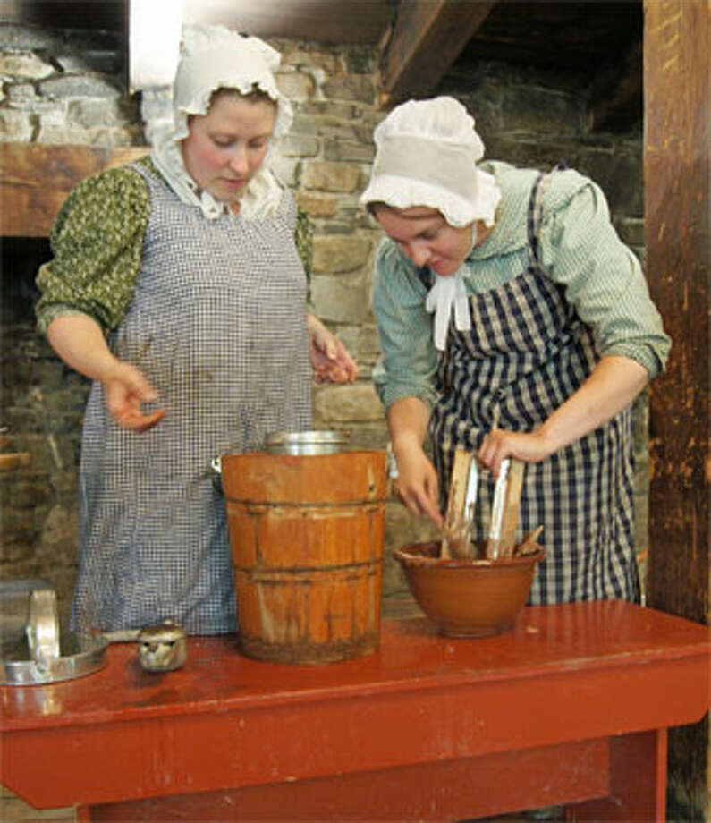 Women at Old Sturbridge Village making ice cream with the hand-cranking method, as was done in the 1830s.