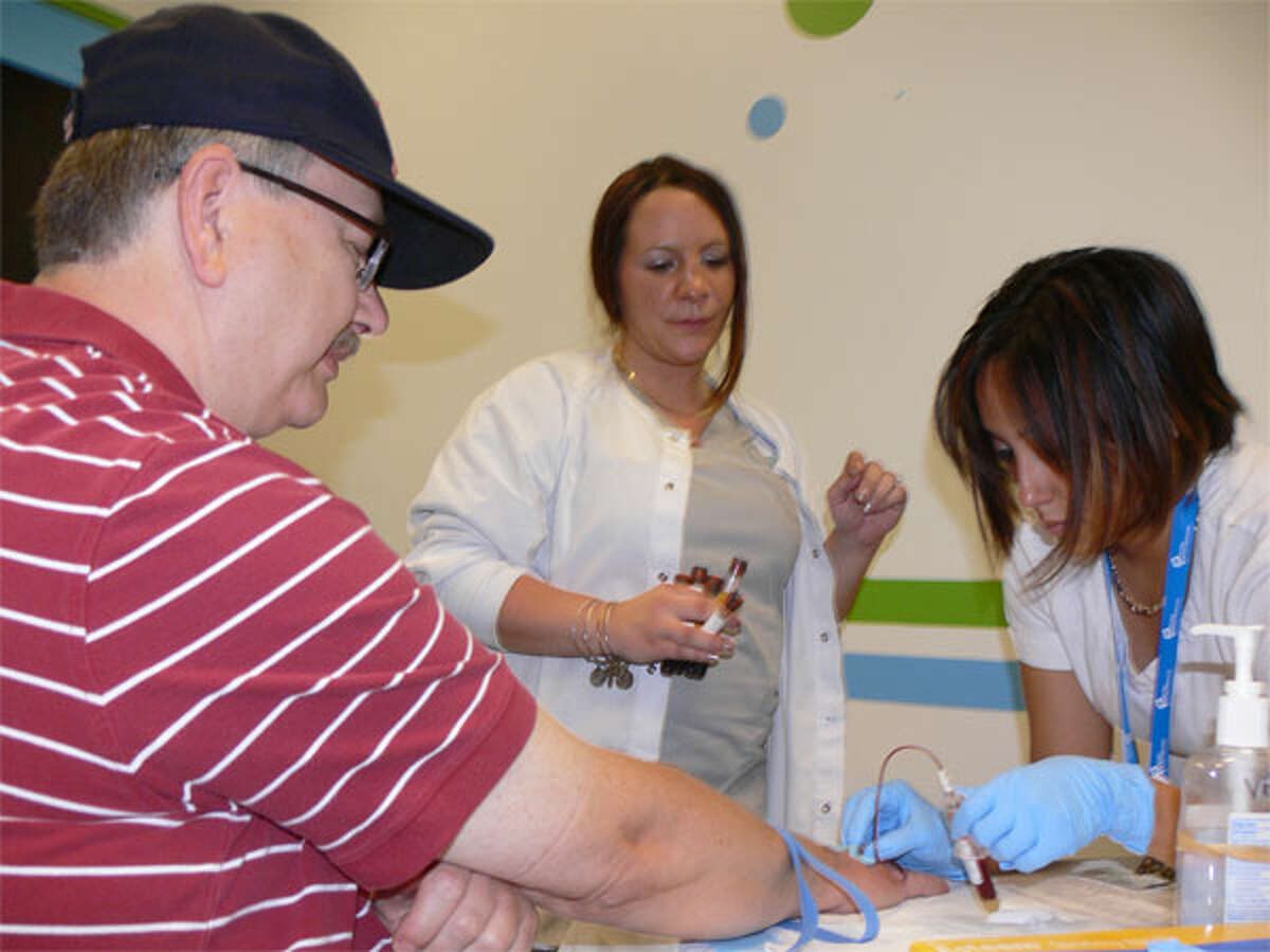 Clint Richards gets his blood drawn for a PSA test by medical assistant Diana Campos, right, with assistance from phlebotomist Lisa Gavrish, during the 2013 Griffin Hospital Men's Health Day at the Sports Center of Connecticut in Shelton.
