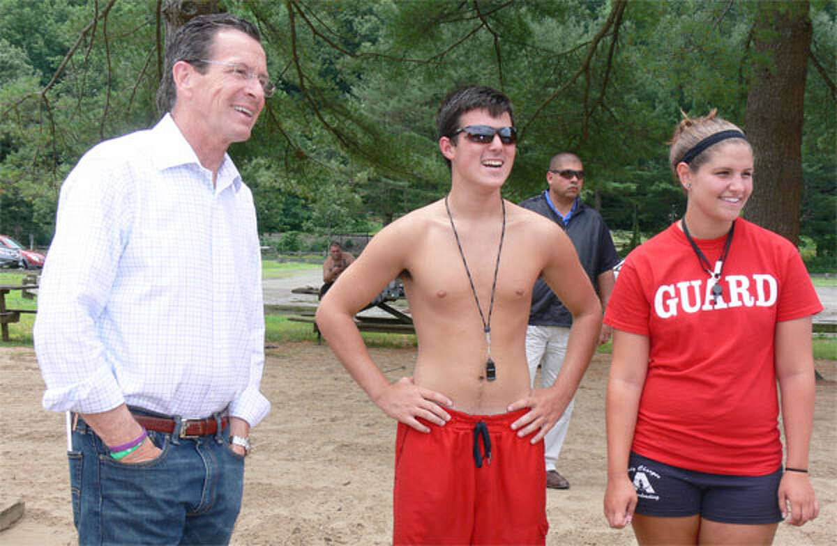 Gov. Dannel P. Malloy enjoys a lighter moment at Indian Well State Park in shelton during a 2013 visit, joined by lifeguards Beau Andrea, 17, of Ansonia, center, and Amber Thomson, 18, of Ansonia.
