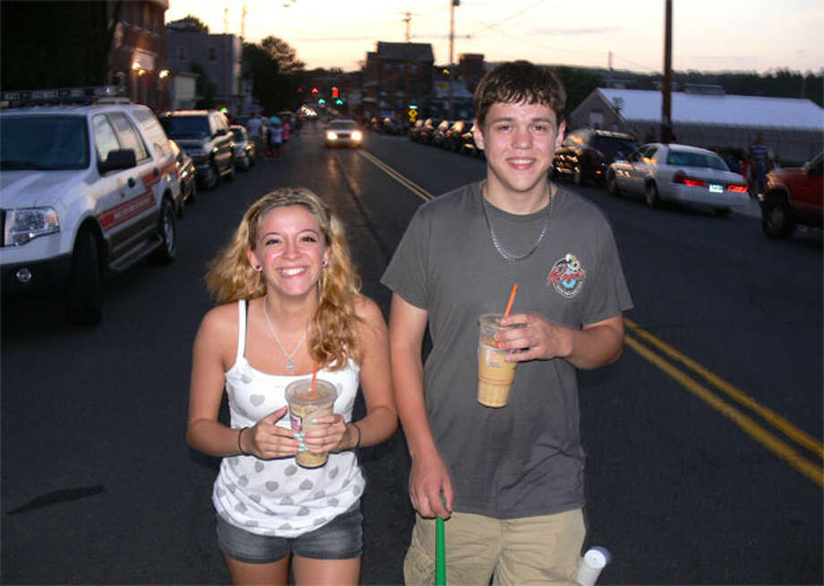 Friends Selena Carde, 16, and Matthew Griffin, 19, both of Shelton, walk down Howe Avenue as fireworks show time nears. The road had been closed to all non-emergency vehicles. (Photo by Brad Durrell)