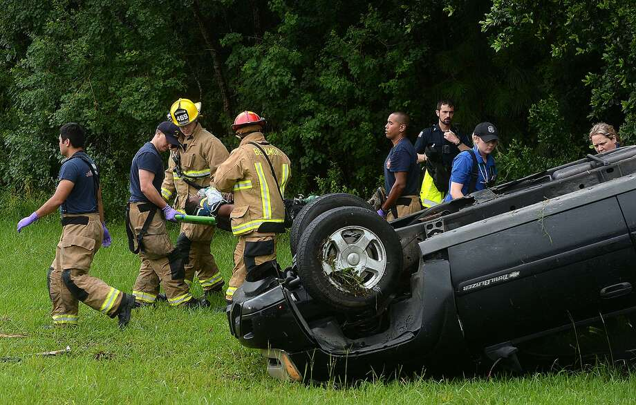 Emergency crews from Beaumont Police, Fire and Rescue and EMS services remove the driver of a Chevy Trailblazer which went off the road and flipped in the grassy area nearby the entry to Highway 96 south at Interstate 10. Traffic westbound on I-10 and at the 96 south entry was slowed as crews responded at the scene. Photo taken Wednesday, June 5, 2019 Kim Brent/The Enterprise Photo: Kim Brent / The Enterprise / BEN