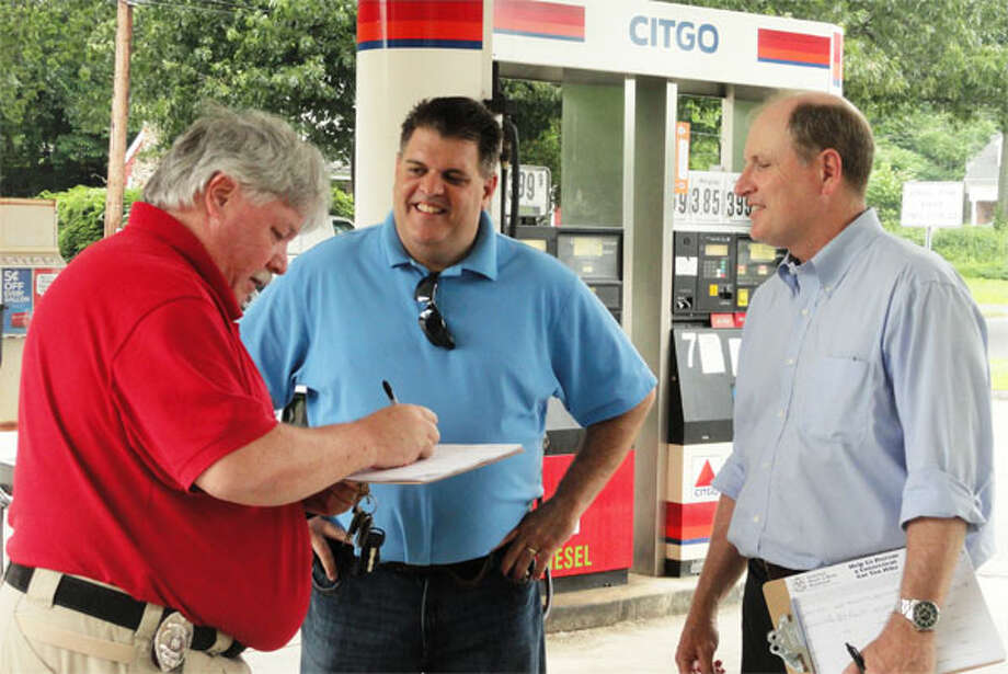 State Sen. Kevin Kelly, right, and state Rep. Dave Rutigliano, center, collect signatures opposing a gas tax increase at a Shelton gas station.