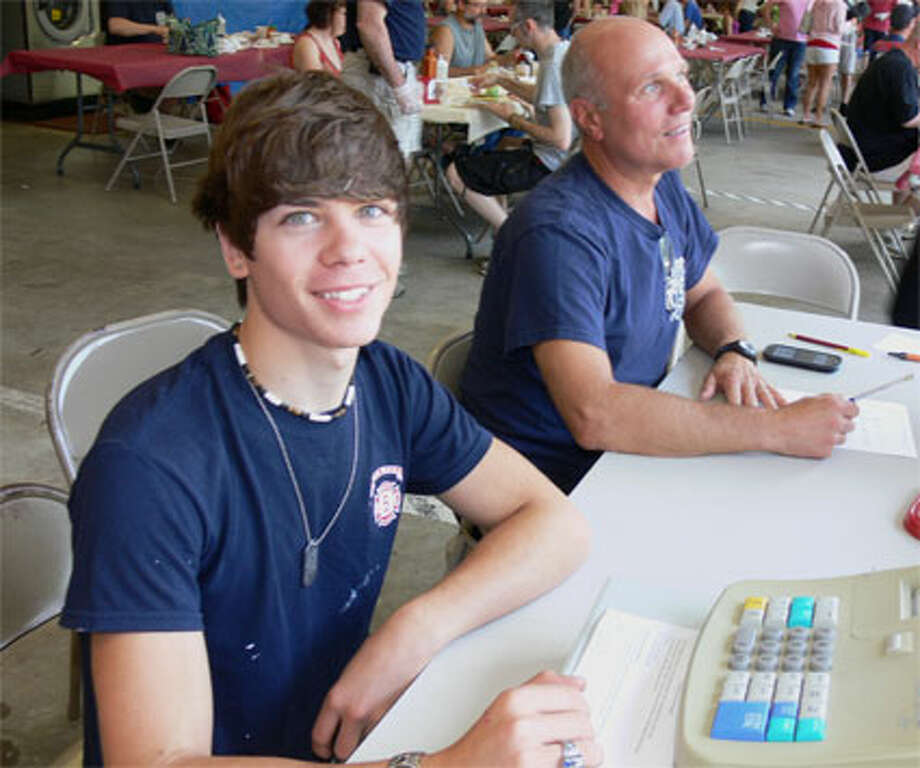 Firefighters Andrew Kopac, 19, left, and Ken Baldyga work the front desk during the White Hills Voluntary Fire Company fund-raising breakfast.