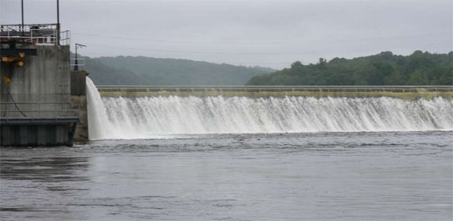 Water flows quickly over the Ousatonic Dam between Shelton and Derby on the Housatonic River, as viewed from the Shelton side near Canal Street.