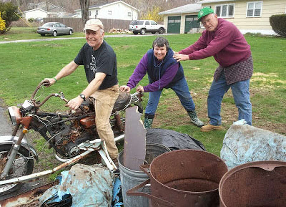 Shelton Land Trust members with an old motorcycle pulled from the woods during the Clean Sweep.