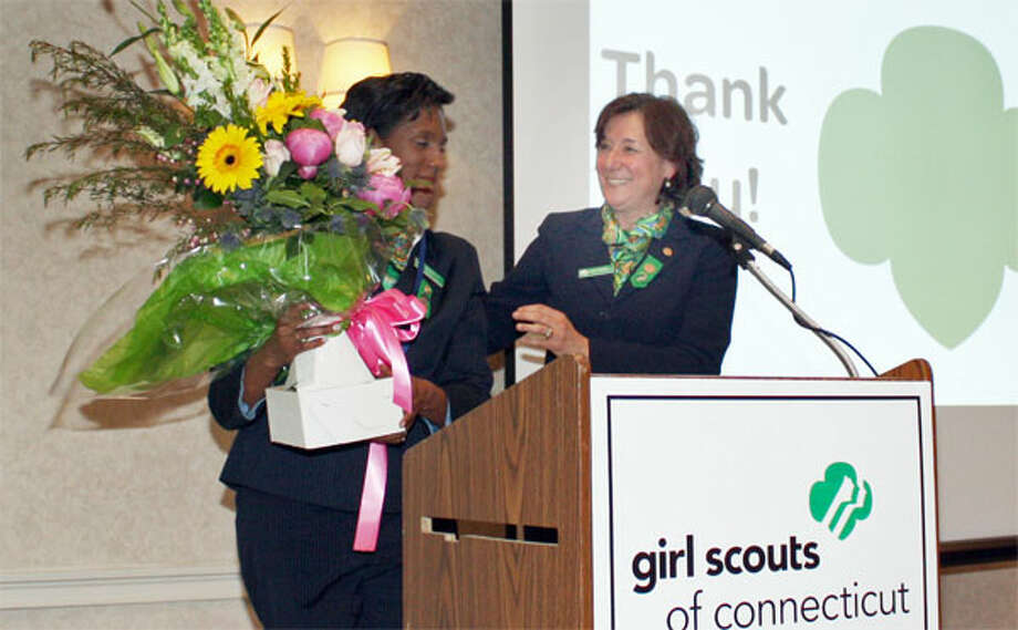 Outgoing Girl Scouts of Connecticut board President Teresa C. Younger of Shelton, left, receives a floral bouquet to recognize her volunteer service from the organization's CEO, Mary Barneby.