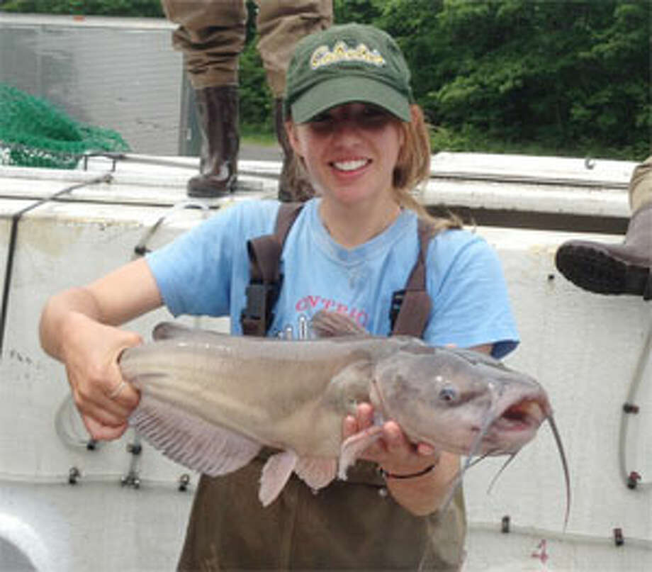 An angler holds up a catfish she caught in a Connecticut lake.