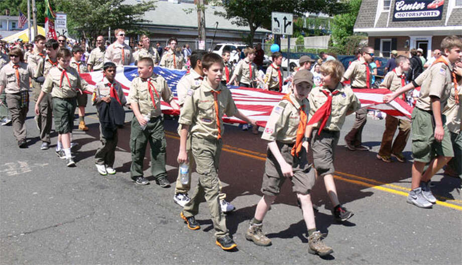 A Shelton Boy Scout troop holds a large American flag while marching on Center Street in the 2013 Memorial Day parade.