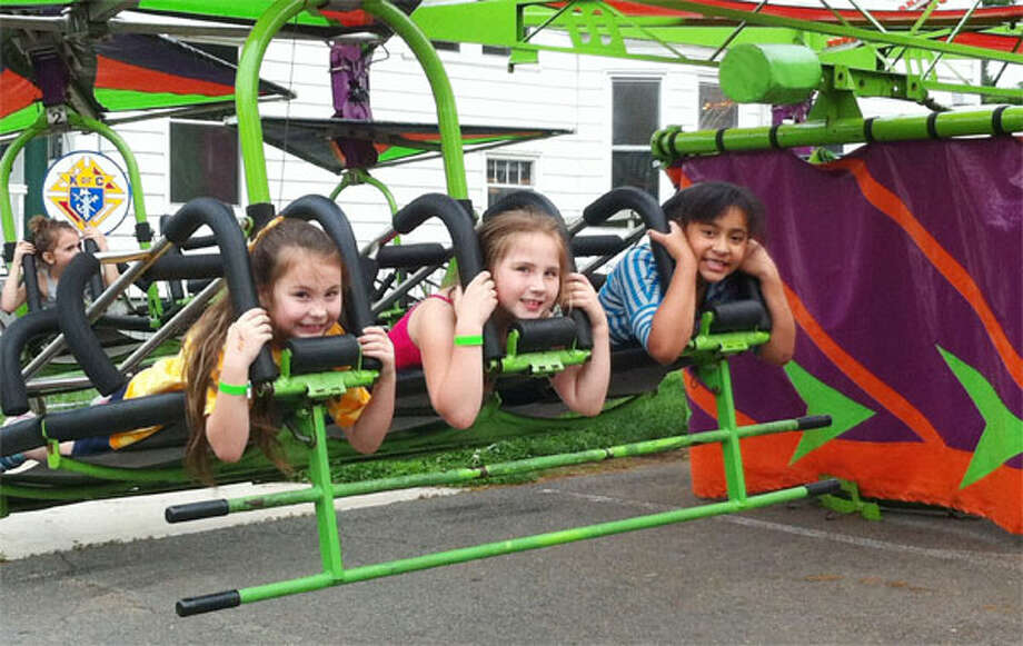 Going for a ride at the 2013 St. Joseph Carnival in Shelton are, from left, Emma Eschweiler, 7; Tatiana Bell, 7; and Natalia Ryzdik, 7, all of Shelton.