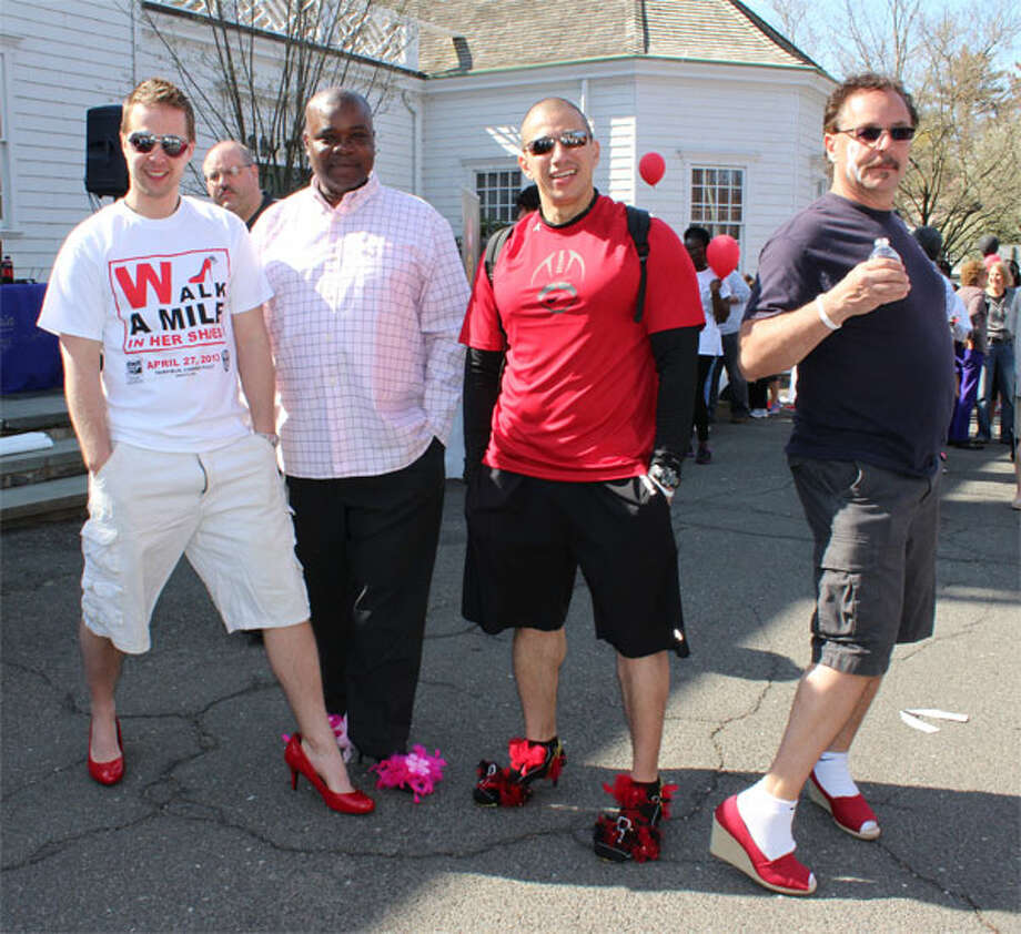 Among those donning feminine footwear for Walk a Mile in Her Shoes on April 27 in Fairfield are, from left, Daniel Chizmadia of Shelton, from Leadership Greater Bridgeport; Martin Goodrich of Bridgeport, Raul Barada of Bridgeport, both from St. Vincent's Special Needs; and Bill Truini of Monroe, from the Stepney Fire Department. (Photo by John Kovach)