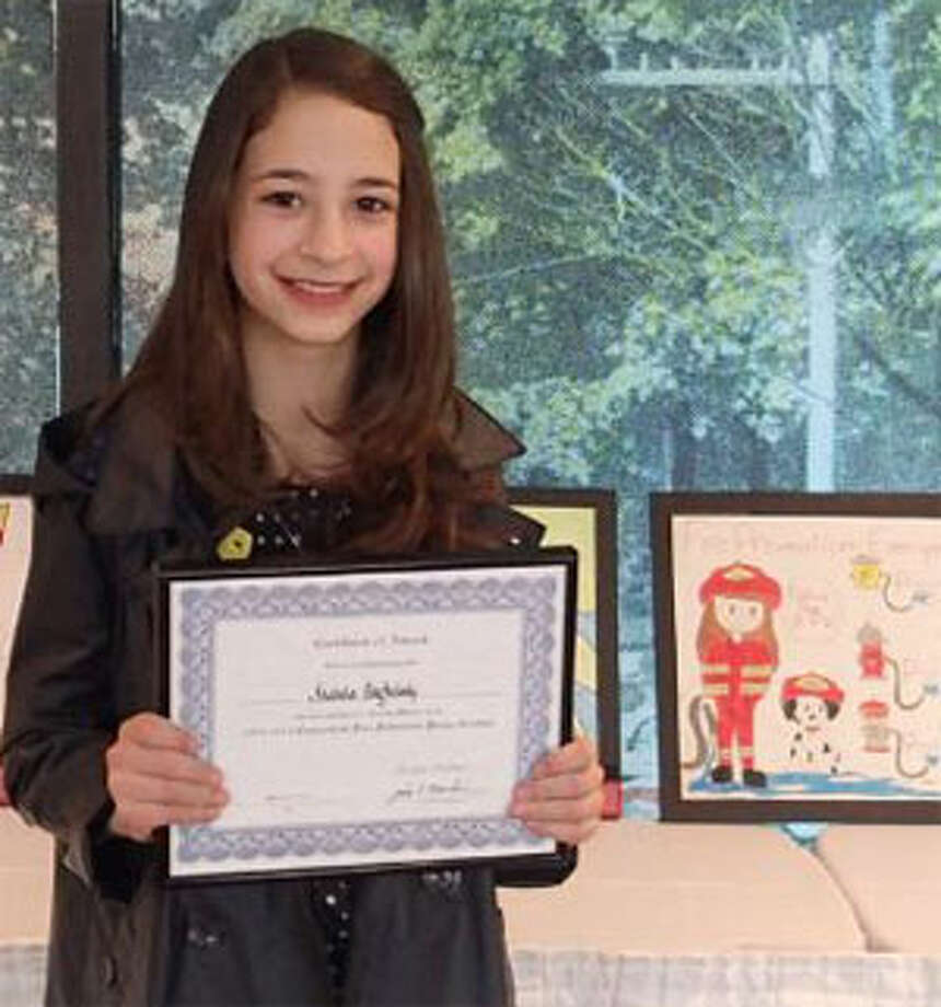 Isabela Baghdady, a St. Lawrence School fifth grader, holds her award certificate near the framed fire prevention poster she designed.