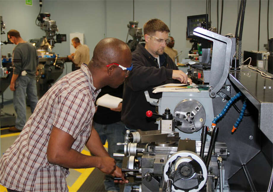 Pierre Antoine, left, and Brett O'Brien train in Housatonic Community College's Advanced Manufacturing Center.