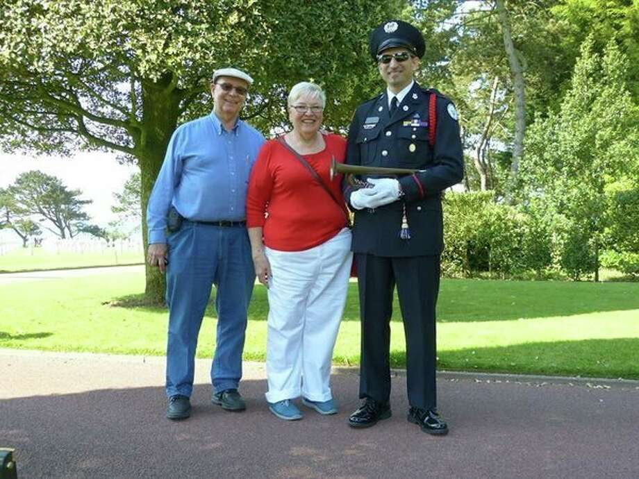 From left, Ken Bow, Judy Bow and Stephen Bow at the Normandy American Cemetery and Memorial in Normandy, France. Stephen, a member of Bugles Across America, is holding a bugle from World War II. Made of Tenite, the bugle was light and easy to carry by a paratrooper.