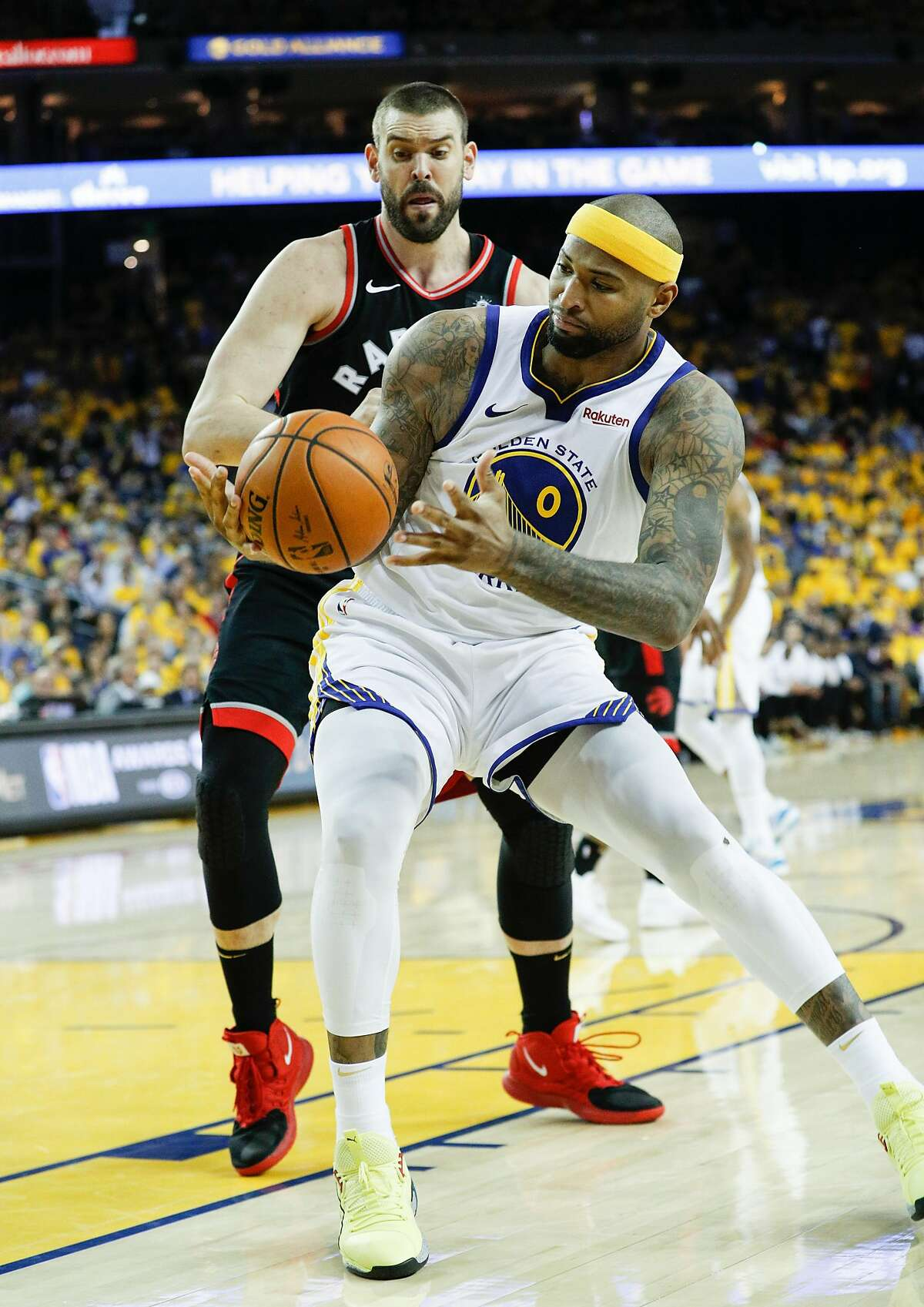 Golden State Warriors' DeMarcus Cousins grabs the ball in front of Toronto Raptors'Marc Gasol in the third quarter during game 3 of the NBA Finals between the Golden State Warriors and the Toronto Raptors at Oracle Arena on Wednesday, June 5, 2019 in Oakland, Calif.
