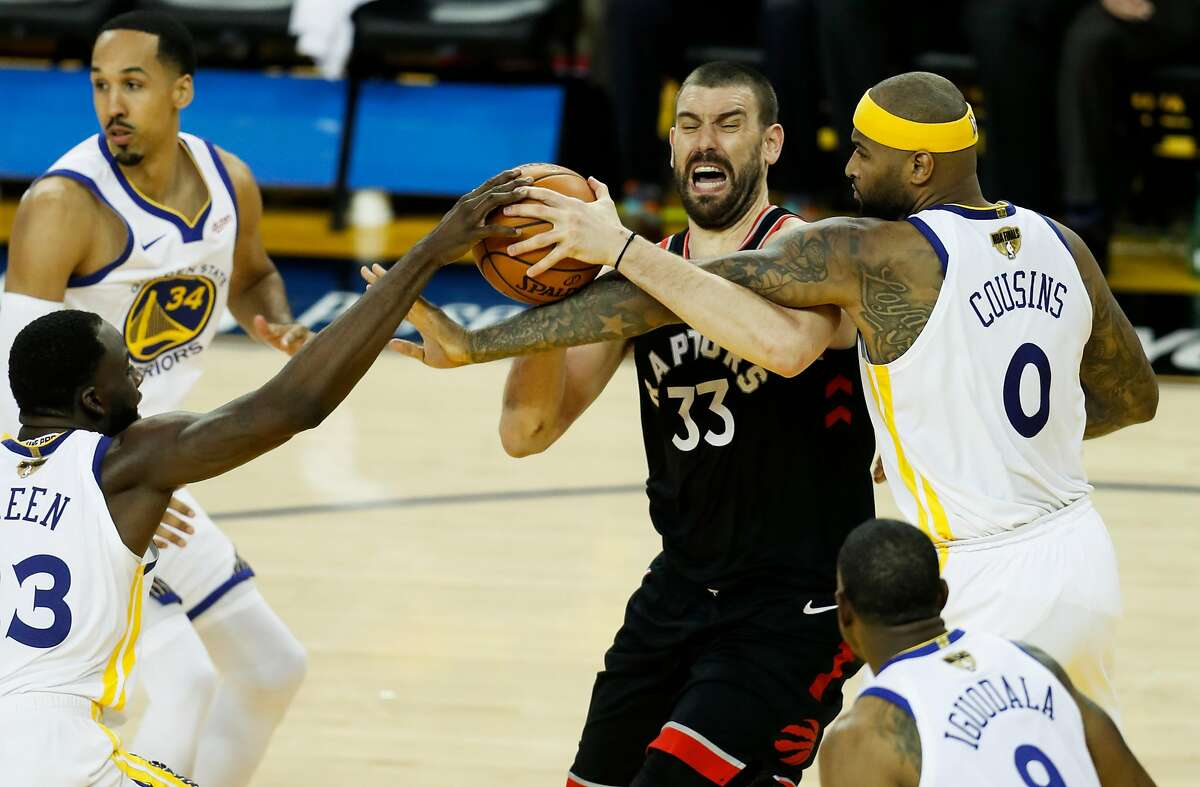 Golden State Warriors' Draymond Green and DeMarcus Cousins defend against Toronto Raptors' Marc Gasol /3 during game 3 of the NBA Finals between the Golden State Warriors and the Toronto Raptors at Scotiabank Arena on Wednesday, June 5, 2019 in Oakland, Calif.