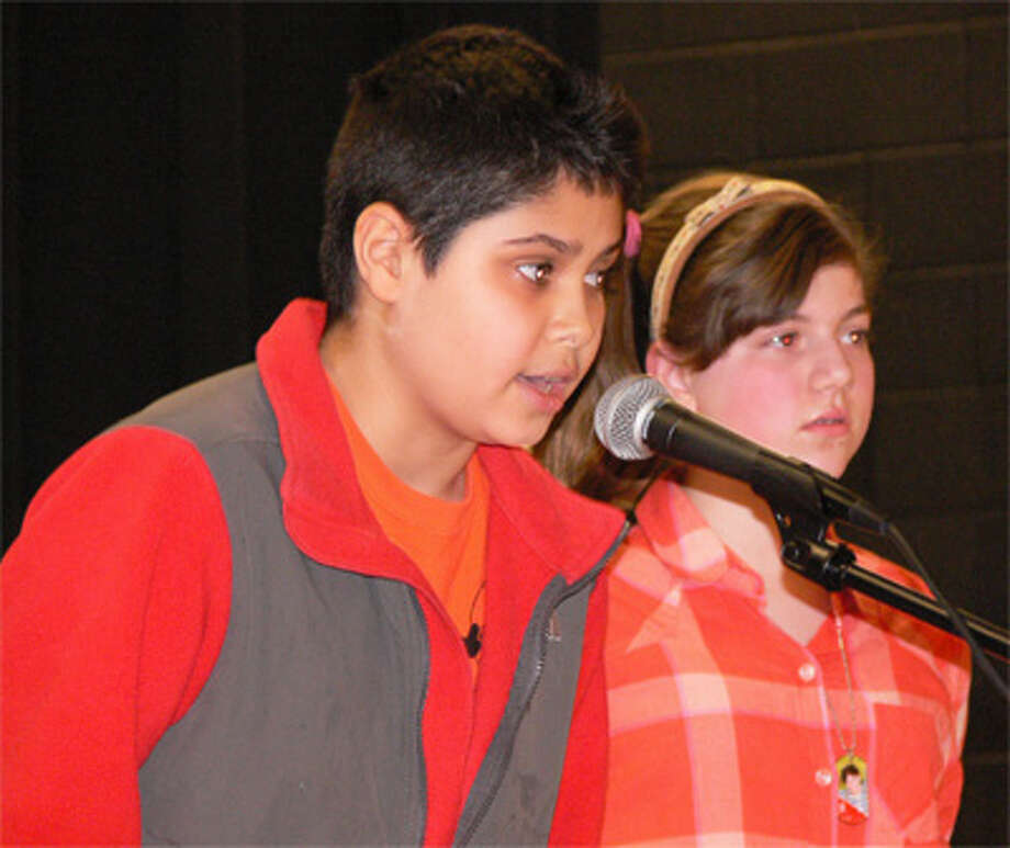 Winner Kamil Alkaul, left, spells a word with runner-up Megan Bisson in the background.