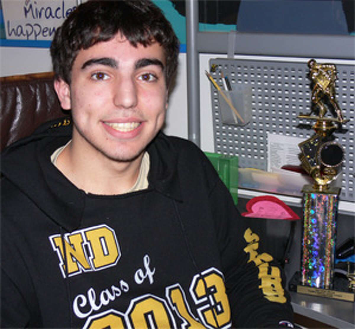 Taylor Chavez, whose story of excelling despite having ADD, next to a hockey trophy in his bedroom.