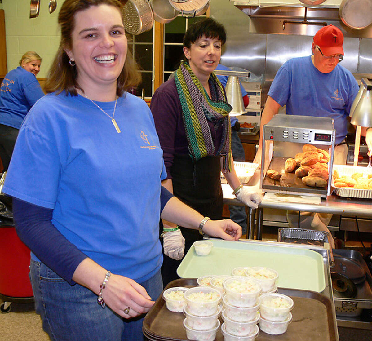 At a previous fish fry, the Rev. Heather Sinclair checks out the kitchen but spent much of her time interacting with guests in the dining room.