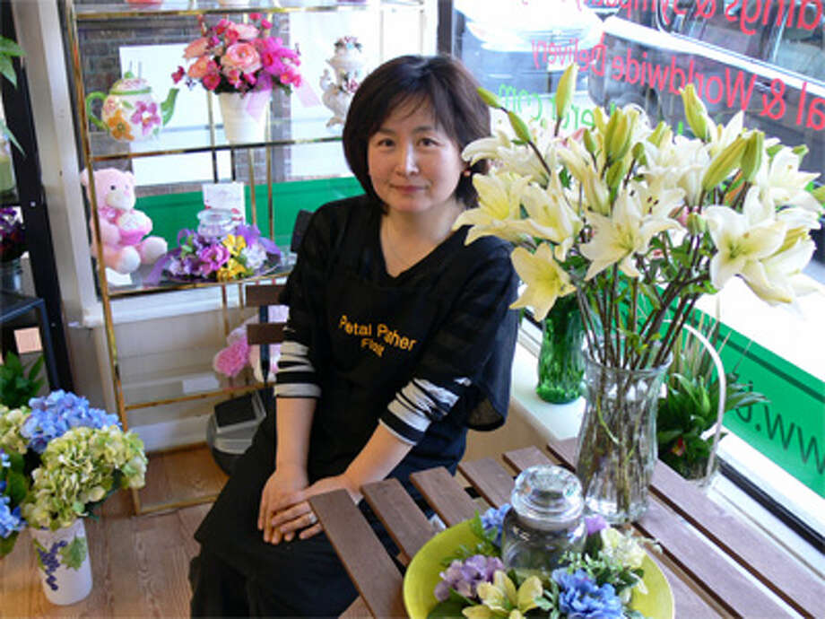 Florist shop owner Annie Hwang sits inside the new location for Petal Pusher Florist, a Shelton business impacted by the downtown fire in early January.