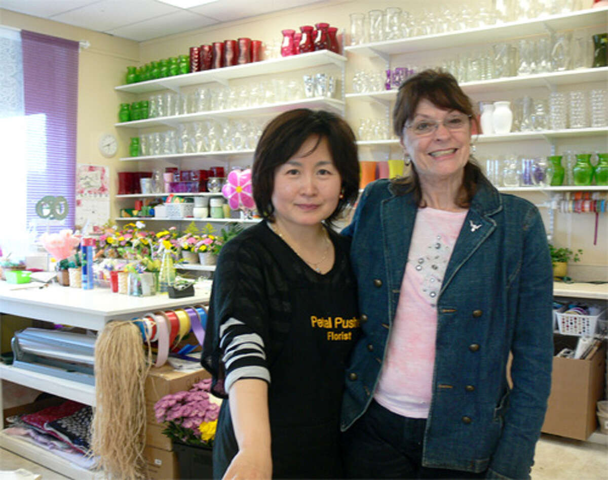 Petal Pusher Florist owner Annie Hwang with Rosemary McClain of Shelton, who works part-time at the store, which has reopened in downtown Derby.