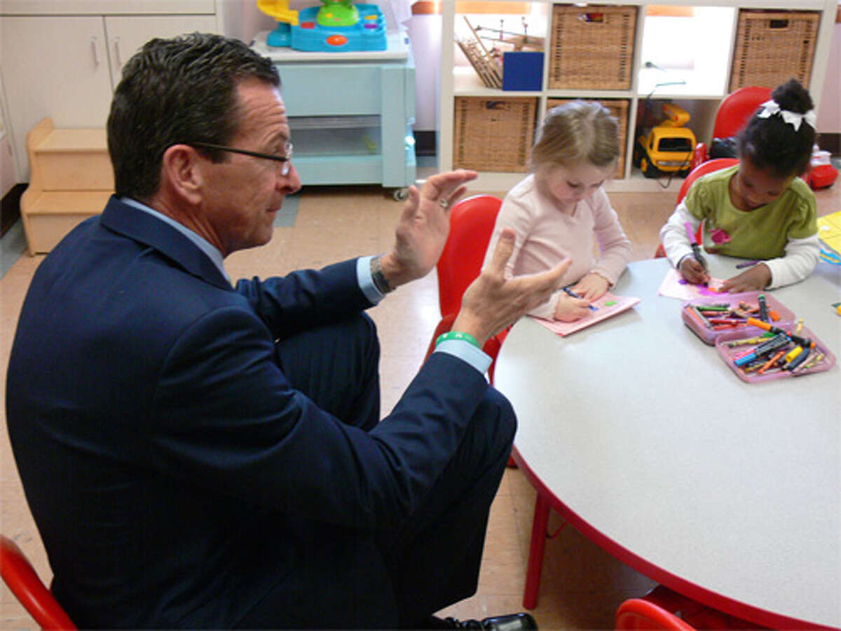 Gov. Dannel P. Malloy claps during a song in the classroom of Sylvie Lobsenz, who operates a language program at the Susanna Wesley School in Shelton.