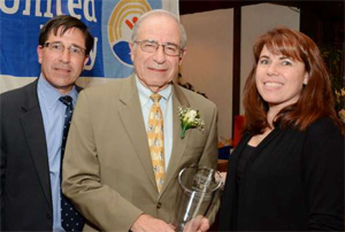 Joe Andreana, center, holds the Charles H. Flynn Humanitarian Award while joined by his son Michael and daughter Michelle.