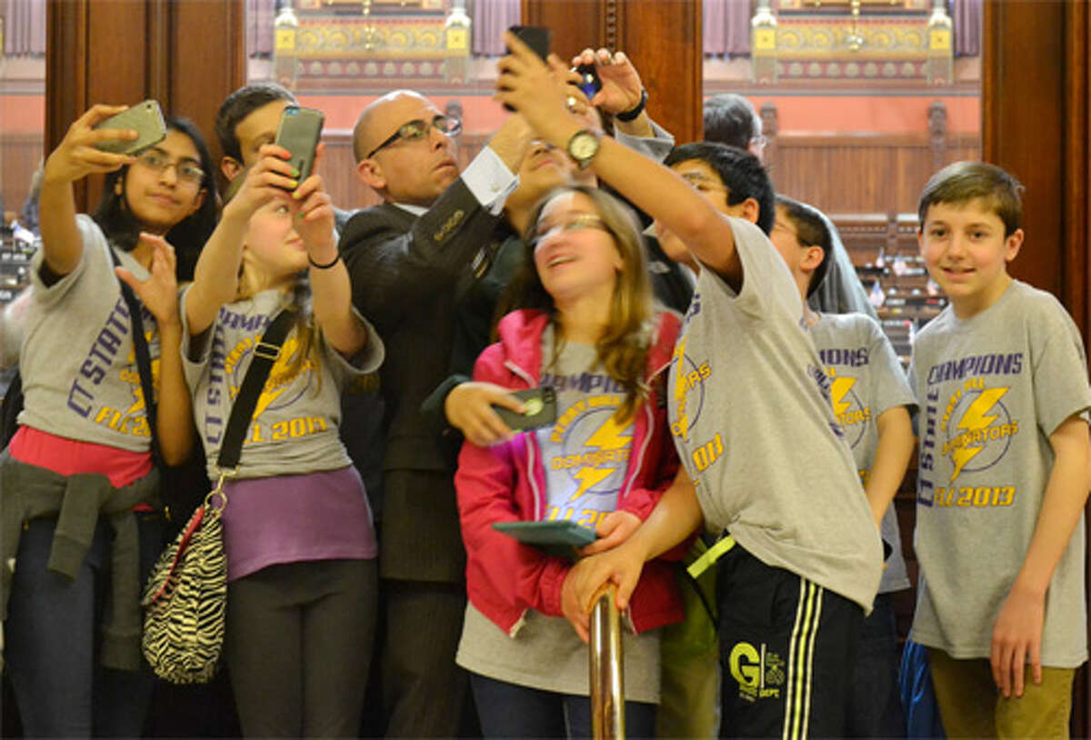 Members of the state champion Perry Hill Dominators from Shelton take selfies with state Rep. Jason Perillo at the Capitol.