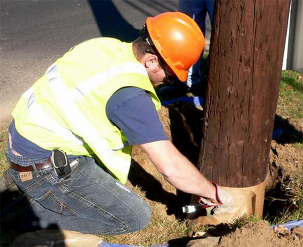 A worker wraps a United Illuminating pole's base after treating it with a chemical agent to prevent decay.